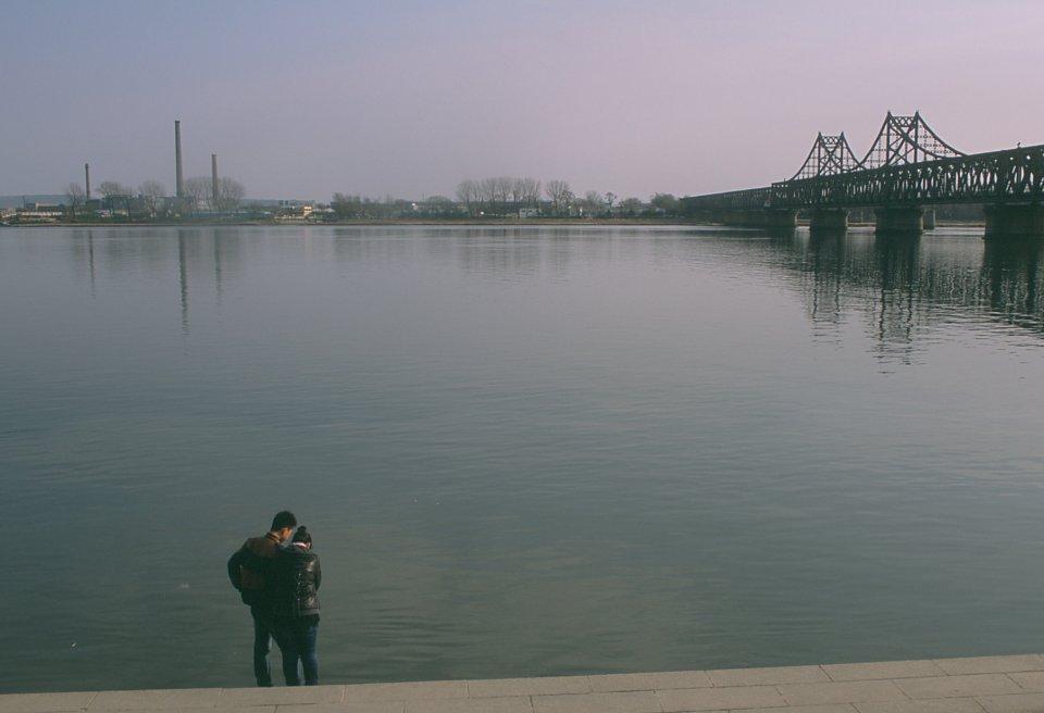 Couple au bord du Yalu. En face, la Corée du Nord